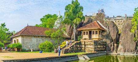 ANURADHAPURA, SRI LANKA - NOVEMBER 26, 2016: The complex of Isurumuniya Viharaya with the view on the Rock Temple, pond and the Stupa, hidden behind the trees, on November 11 in Anuradhapura.