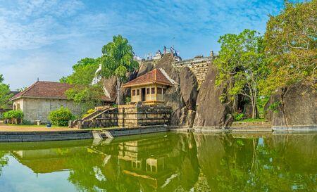 The sacred Rock and old Temple of Isurumuniya Viharaya reflect in large pond, Anuradhapura, Sri Lanka. Stock Photo