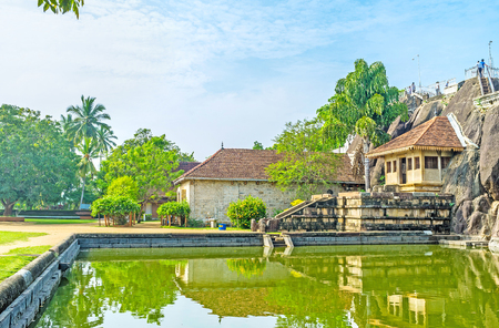 temple tank: The Isurumuniya Rock Temple surrounded by green garden with a pond at the foot of sacred Rock, Anuradhapura, Sri Lanka. Stock Photo