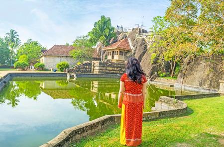 The young tourist at the bank of the pond of Isurumuniya Viharaya, wathes the Rock Temple in shade of trees, Anuradhapura, Sri Lanka.
