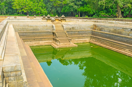 The Twin Pools with high granite walls, stairs and carved decorations located in lush garden, Anuradhapura, Sri Lanka.