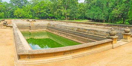 Panorama of ancient Kuttam Pokuna - Twin Ponds with granite walls and decorations, surrounded by lush garden, Anuradhapura, Sri Lanka. Stock Photo