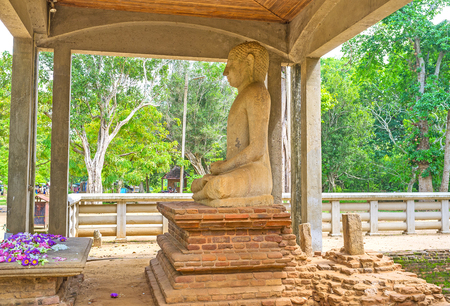 The Samadhi Buddha Statue in pose of meditation is the place of veneration, surrounded by ancient ruins and greenery of Mahamevnawa Park, Anuradhapura, Sri Lanka.