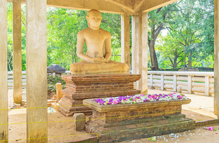 buddha sri lanka: The meditating Samadhi Buddha Statue with the colorful lotus flowers on the altar, Anuradhapura, Sri Lanka. Stock Photo