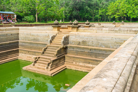The massive granite walls of the Twin Pools with the scenic carved stairs and decorative pots, Anuradhapura, Sri Lanka.