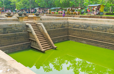 temple tank: ANURADHAPURA, SRI LANKA - NOVEMBER 26, 2016: The embankment of the Twin Pools occupied with the tourist stalls, offering handmade souvenirs and fresh beverages, on November 26 in Anuradhapura.