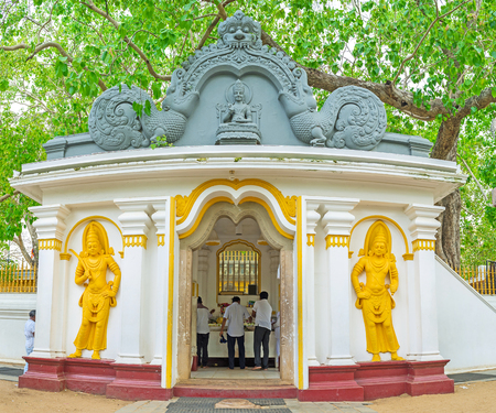 vihara: The Bodhi Tree Shrine of Jaya Sri Maha Bodhi Temple decorated with colorful sculptures, reliefs and carved patterns, the branches of Sacred Fig rise above its roof, Anuradhapura, Sri Lanka.