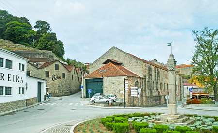 PORTO, PORTUGAL - APRIL 30, 2012: The small square in Vila Nova de Gaia, surrounded by historic wine factories and lodges, offering tourists to visit their cellars, on April 30 in Porto.