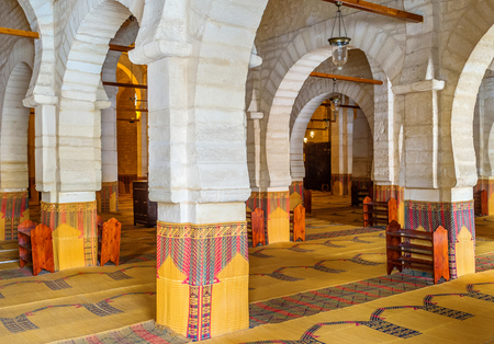 prayer rug: SOUSSE, TUNISIA - SEPTEMBER 6, 2015: The large prayer hall of the Grand Mosque is separated into the narrow areas by the huge stone arcades, on September 6 in Sousse. Editorial