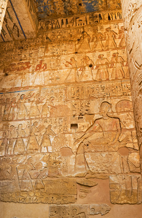eligion: The ancient relief depicts the Pharaoh and his  subjects, bringing him riches, Habu Temple, Luxor, Egypt. Editorial