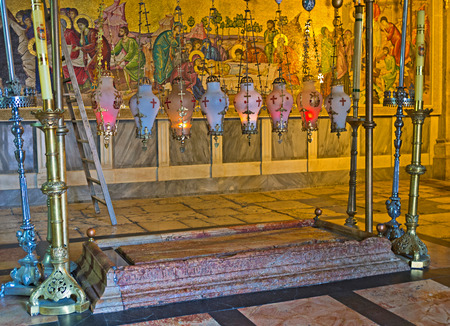 JERUSALEM, ISRAEL - FEBRUARY 16, 2016: The Stone of Anointing in the Church of the Holy Sepulchre with the mosaic icon on the background, depicting how Jesus body was prepared for burial, on February 16 in Jerusalem.