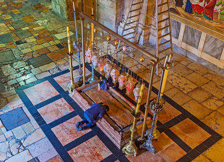 JERUSALEM, ISRAEL - FEBRUARY 16, 2016: The man prays on the knees near the Stone of Anointing in the Church of the Holy Sepulchre, on February 16 in Jerusalem.