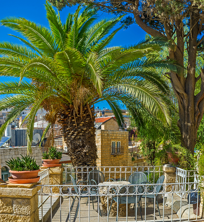 The tiny table under the lush palm tree is perfect for the midday coffee with the view on the Muslim Quarter, Jerusalem, Israel.