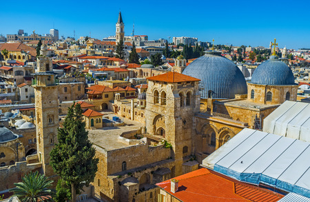 The grey domes and bell tower of the Church of the Holy Sepulchre and the slender minaret of the Mosque of Omar seen from the bell tower of the Lutheran Kirche of the Redeemer, Israel.