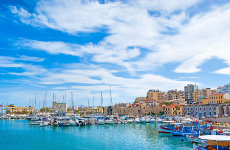 The walk along the harbor of Heraklion with ruins of Venetian era buildings and numerous yachts and boats in port, Crete, Greece.