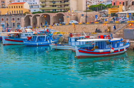 HERAKLION, GREECE - OCTOBER 16, 2013: The evening port is the crowded place, full of tourists and fishermen, on October 16 in Heraklion.