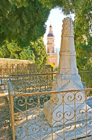 basillica: The gravestone on the Old Castle Hill Cemetery, surrounded by lush greenery and with the bell tower of Saint-Michel Basillica on the background, Menton, France.