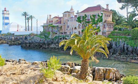 marta: The tiny rocky bay is the nice place to walk and enjoy the historic Villa of Santa Maria and beautiful Santa Marta lighthouse, Cascais, Portugal. Stock Photo