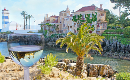 marta: The scenic Santa Marta lighthouse and the Villa of Santa Maria, on the rocky bay, reflect in glass of white wine, Cascais, Portugal.