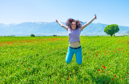 The young girl jumps on the poppy field and laughs, Samarkand suburb, Uzbekistan. Stock Photo