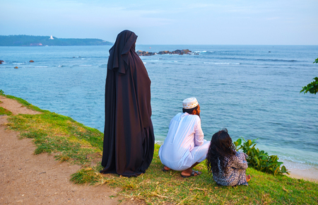 GALLE, SRI LANKA - DECEMBER 3, 2016: The muslim family with children watches the ocean from the top of the medieval forts wall, on December 3 in Galle.