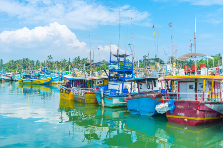 fischerei: MIRISSA, SRI LANKA - DECEMBER 3, 2016: The old fisheries harbor is the notable tourist landmark, popular among the visitors, enjoying the old colorful boats, tilted on each other, on December 3 in Mirissa. Editorial
