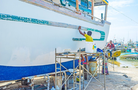 fischerei: MIRISSA, SRI LANKA - DECEMBER 3, 2016: The fishermen remove the old paint from their fishing trawler at the Fisheries Harbor, on December 3 in Mirissa.