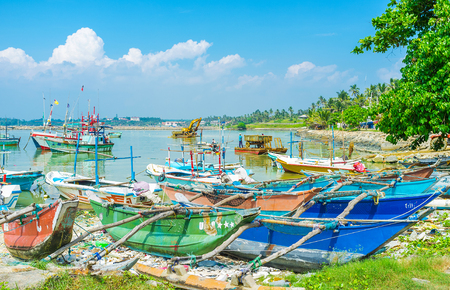 fischerei: MIRISSA, SRI LANKA - DECEMBER 3, 2016: The old catamaran boats at shore of the fisheries harbor and the amphibious excavator, dredging the ports bed on background, on December 3 in Mirissa.