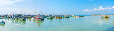 The large fisheries harbor, full of boats and trawlers, and excavator, dredging the ports bed, on background, Mirissa, Sri Lanka.