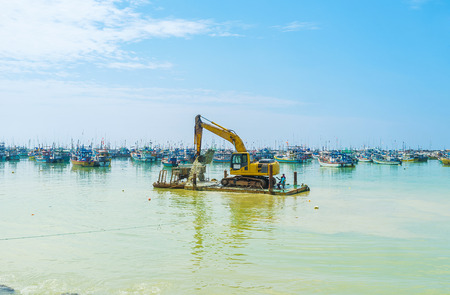 The amphibious excavator works to dredge bed in old fisheries harbor, Mirissa, Sri Lanka.
