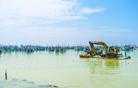 MIRISSA, SRI LANKA - DECEMBER 3, 2016: The amphibious excavator loads the ground to the floating cargo trailer, on December 3 in Mirissa.