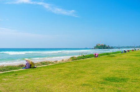 sunshade: The Beach Road is the popular destination among the young couples, sitting here under umbrellas and enjoy romance with a view on Parey Dewa Island Temple, Matara, Sri Lanka.