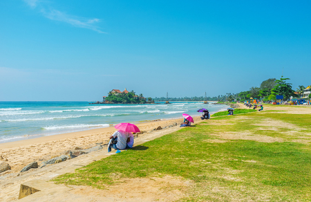 sunshade: The best way to spend the free time in Matara is to visit Beach Road, one of the most romantic places at resort, famous among local young couples, Sri Lanka. Stock Photo