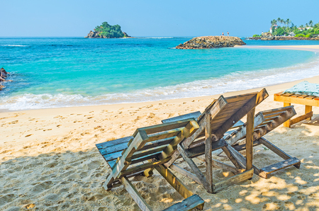 devils garden: The wooden beach chairs, stand in shade and are the best choice to relax with amazing views, Midigama, Sri Lanka.