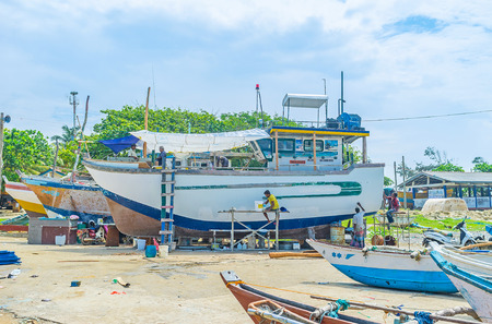 MIRISSA, SRI LANKA - DECEMBER 3, 2016: The fishermen repair and paint their trawler at the shore of the large fisheries harbor, on December 3 in Mirissa. Editorial