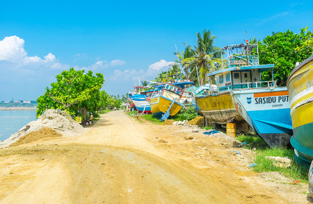 MIRISSA, SRI LANKA - DECEMBER 3, 2016: The footpath at the shore of fisheries harbor with old boats, weiting for repair, on December 3 in Mirissa.