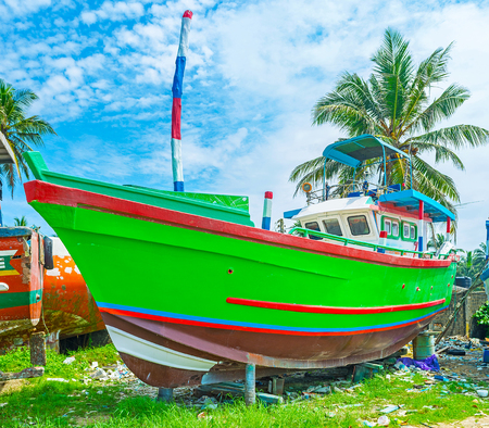 The bright newly painted boat dries at the shore of fisheries harbor of Mirissa, Sri Lanka.