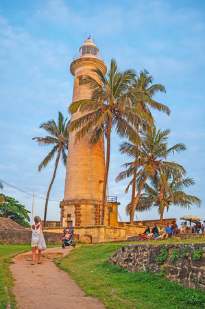GALLE, SRI LANKA - DECEMBER 3, 2016: The old lighthouse, surrounded by palms, is one of the popular tourist places, on December 3 in Galle. Editorial