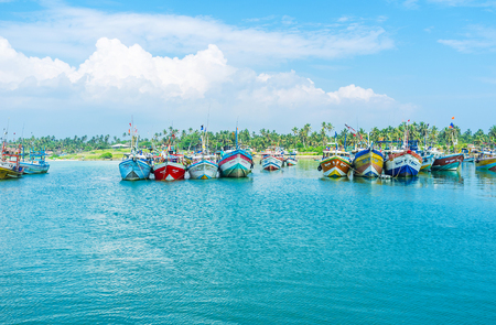 MIRISSA, SRI LANKA - DECEMBER 3, 2016: The colorful fishing boats, surrounded by bright blue waters of the harbor, on December 3 in Mirissa.