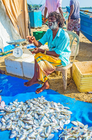 GALLE, SRI LANKA - DECEMBER 3, 2016: The old fish dealer advertises the fresh catch and bargains with customers for the price, on December 3 in Galle. Editorial