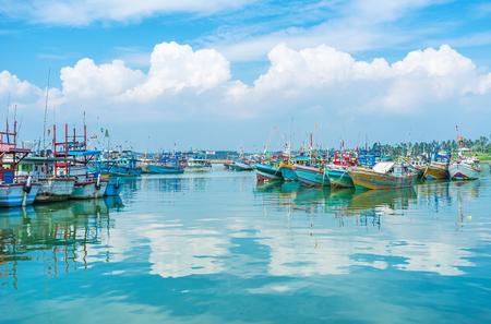 스리랑카 Mirissa의 수산 항구에서 부드러운 파도에 흔들리는 오래 된 다채로운 보트.