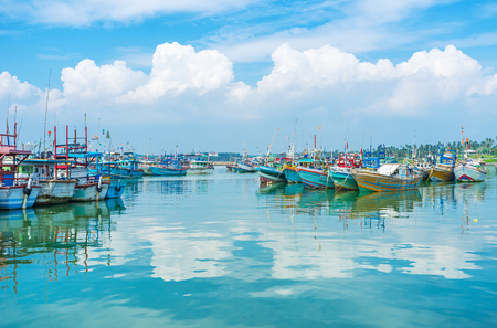 Die alten bunten Boote, die auf den sanften Wellen im Fischereihafen von Mirissa, Sri Lanka schaukeln. Standard-Bild - 70594910