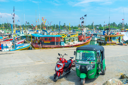 MIRISSA, SRI LANKA - DECEMBER 3, 2016: Tuk tuk and bike are parked at the fisheries harbor, full of trawlers and boats, on December 3 in Mirissa.