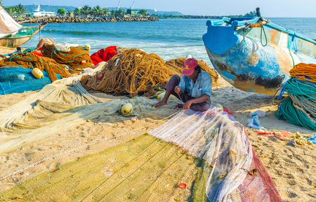 trawler net: GALLE, SRI LANKA - DECEMBER 3, 2016: The fisherman sews the net, sitting next to the old catamaran boat on the sandy beach, on December 3 in Galle.