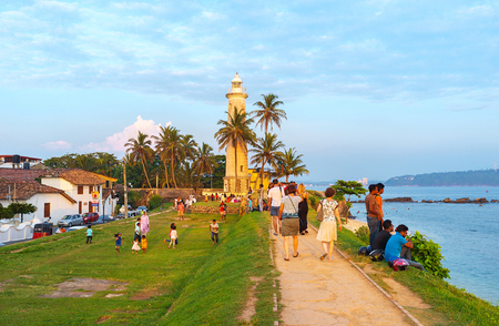 GALLE, SRI LANKA - DECEMBER 3, 2016: The rampart walk is the popular tourist attraction, people enjoy the seascape and city landmarks, on December 3 in Galle.