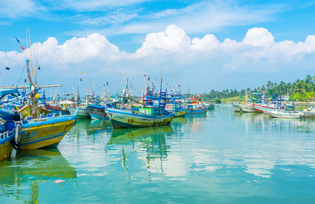 MIRISSA, SRI LANKA - DECEMBER 3, 2016: The fluffy clouds over the fisheries harbor reflect in azure waters next to the shadows of the fishing trawlers, on December 3 in Mirissa.