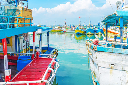fischerei: The view on fisheries harbor through the space between two colorful trawlers, Mirissa, Sri Lanka. Editorial