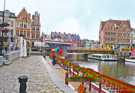 GHENT, BELGIUM - MAY 26, 2011: The Korenlei Quay decorated with flowers and flags and occupied with tourist cafes, offering to relax and enjoy the views of medieval city, on May 26 in Ghent.