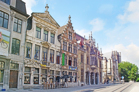 GHENT, BELGIUM - MAY 26, 2011: The medieval buildings at the Sint-Michielshelling street, leading to the bridge across the Leie river and St Michaels Church, on May 26 in Ghent.