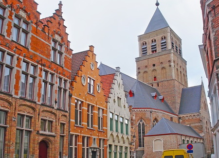 The row of the stepped gables at Sint-Jakobsstraat street with the tall belfry of Early Gothic Sint Jakobskerk (St James or St Jacob) Church on background, Bruges, Belgium.
